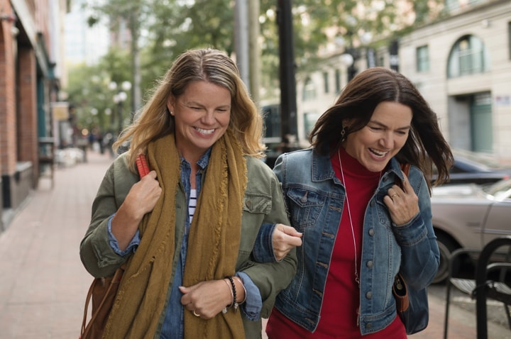 2 women walking together with linked arms
